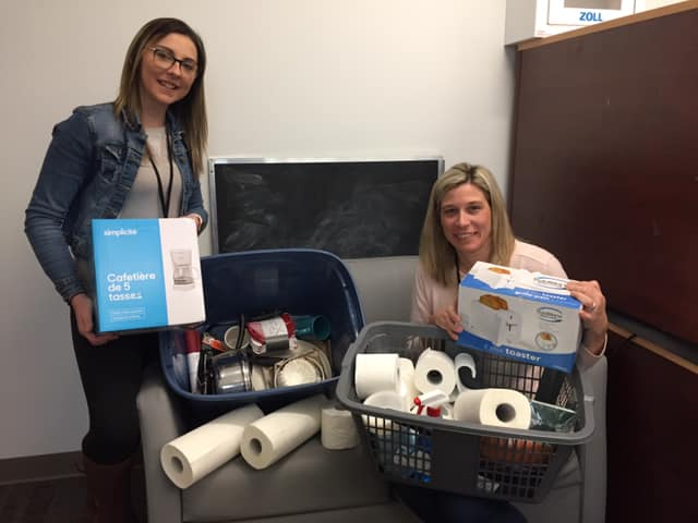 Housing stability workers holding supplied donations for those requiring housing supports.